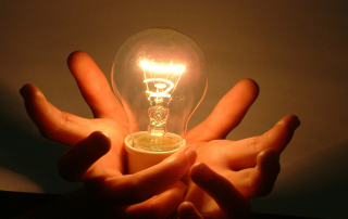 Hands holding a light bulb