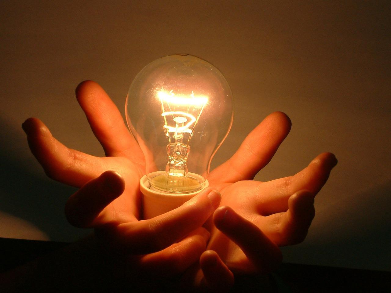 Hands holding a light bulb